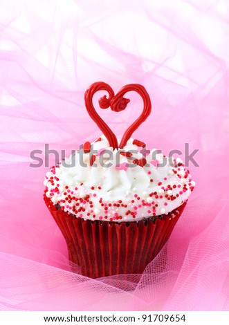 Cupcake decorated with sprinkles and a red chocolate heart - stock photo
