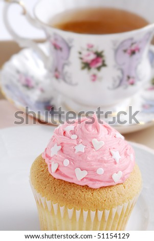 Cupcake frosted in pink with heart and star shape sprinkles - stock photo
