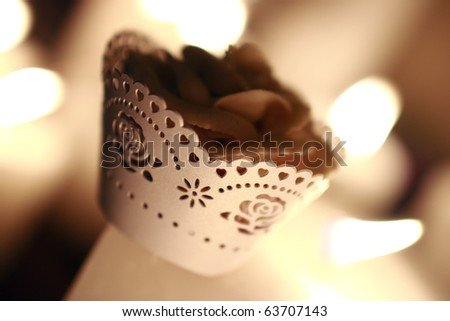 Cupcake in a rose and heart cut-out cupcake sleeve - stock photo