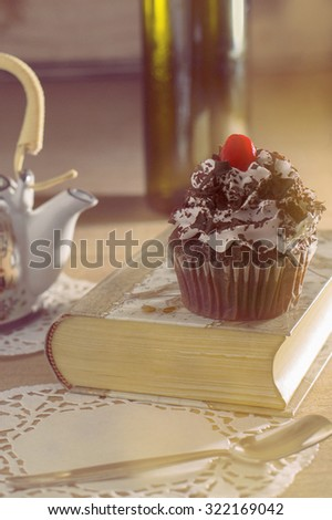 cupcake on a book in a winter afternoon. vintage feel.