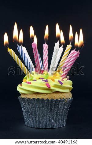 cupcake on black with lots of candles on black - stock photo