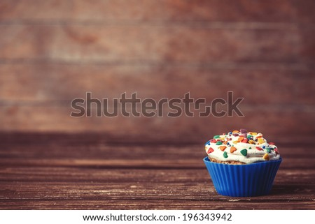 Cupcake on wooden table. - stock photo