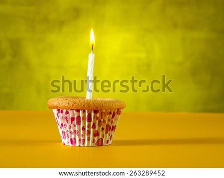 Cupcake on yellow table - stock photo