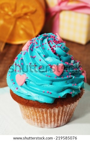 Cupcake - shallow DOF. Gifts in the background. - stock photo