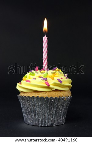 cupcake shot on a black background with one candle - stock photo