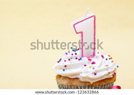 Cupcake with birthday candle of one year old isolated on plain background. - stock photo