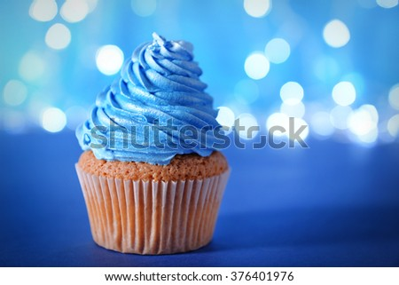 Cupcake with blue cream icing on a glitter background, close up - stock photo