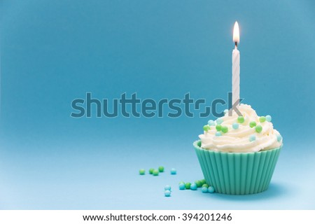 cupcake with burning candle and blue background - stock photo