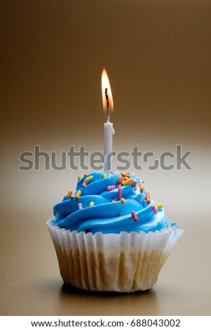 Cupcake with candle on brown background