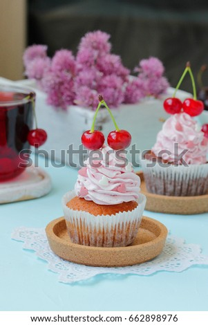 Cupcake with cherry cream and a cherry on top. With a cherry drink. Selective focus.