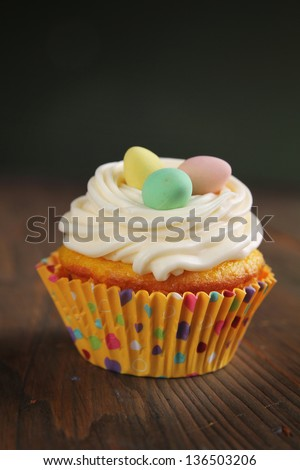 Cupcake with colored eggs on top on a wooden table