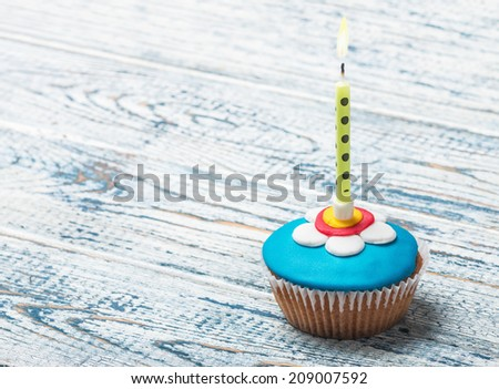 Cupcake with floral decorations and a burning candle on a wooden table - stock photo