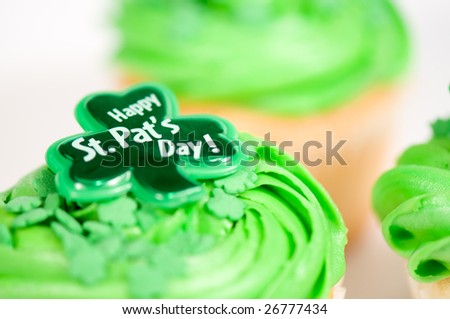 Cupcake with green icing and Happy St-Pat's Day written on it. It is on a white background with other cupcakes in the background.