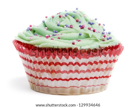 Cupcake with green icing and hundreds and thousands against white background in front of white background