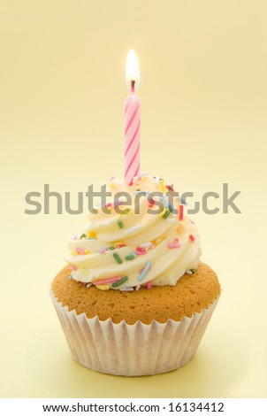 Cupcake with icing and single candle with yellow theme - stock photo