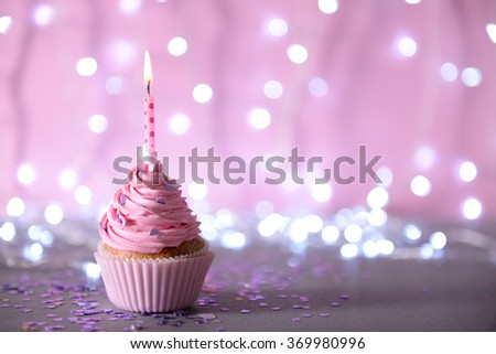Cupcake with pink cream icing and candle on a glitter background - stock photo