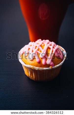 cupcake with pink frosting  and red cup on a wooden background - stock photo