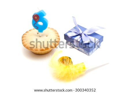 cupcake with six years birthday candle, gift and whistle on white background - stock photo