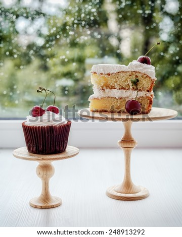 Cupcake with whipped cream and  cake on the stands against window pane in rainy day. - stock photo