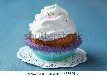 Cupcake with white cream icing and candy sprinkles - stock photo