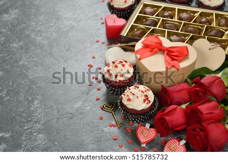 Cupcakes, chocolate and rose on a gray background, the concept of Valentine's Day