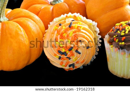 Cupcakes decorated for Halloween surrounded by pumpkins. - stock photo