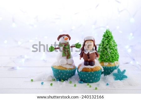 Cupcakes decorated with a sugar kid in a fur hat Snowman and fir on the Christmas lights background. - stock photo