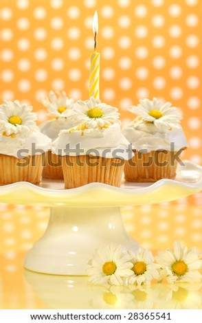 Cupcakes decorated with icing and little daisies on cake tray - stock photo