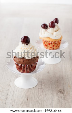 cupcakes decorated with whipped cream and cherries
