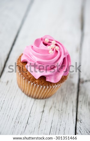 Cupcakes ( muffins ) with pink cream and beads