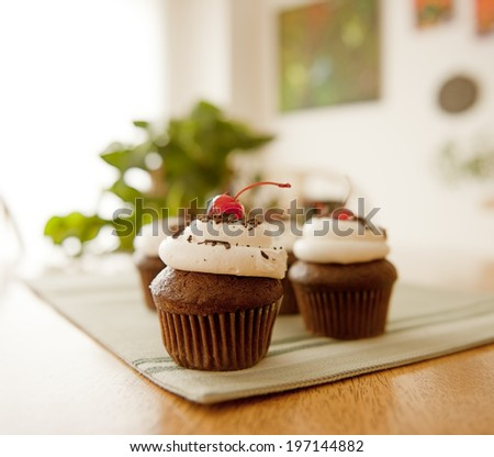 Cupcakes sitting on a mat on top of a wooden table.