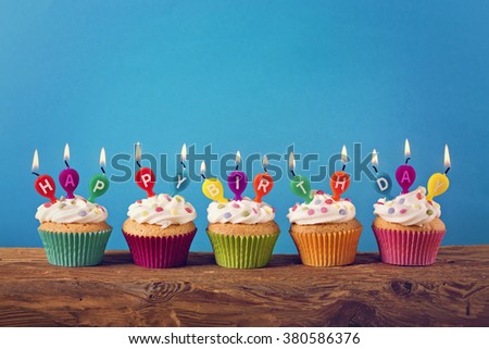 Cupcakes with candles on blue background
