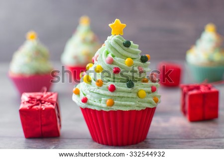Cupcakes with christmas tree shape and christmas decoration on wood - stock photo