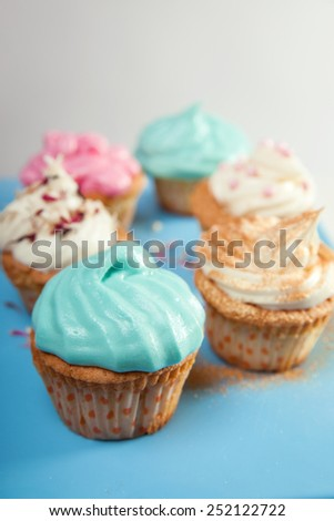 Cupcakes with colorful cream on white and blue background - stock photo