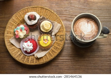 Cupcakes with hot chocolate on old wooden table. - stock photo