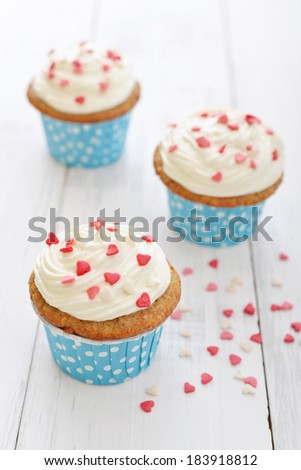 Cupcakes with icing in shape of hearts on wooden background - stock photo