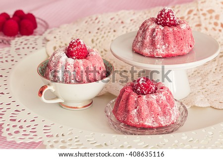 cupcakes with raspberries on a romantic table