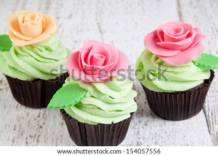 cupcakes with roses on wooden table - stock photo