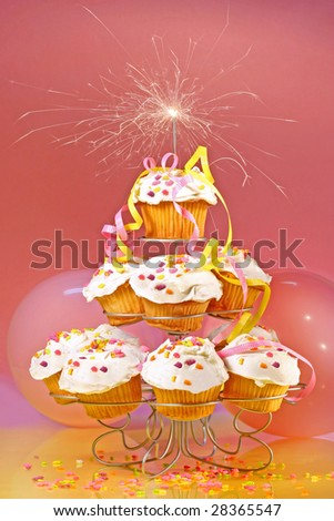 Cupcakes with sparkler on top against pink background - stock photo