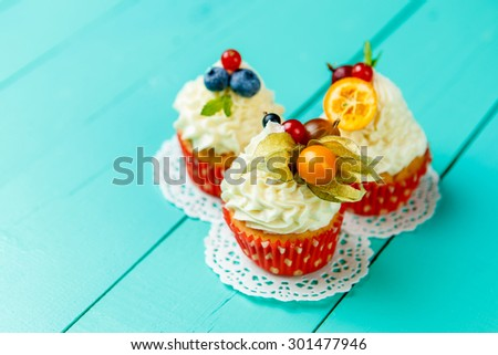 cupcakes with summer berries on blue wooden table