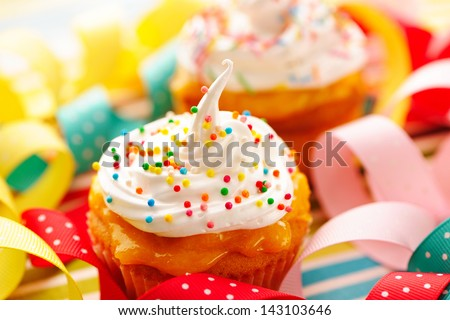 Cupcakes with whipped cream and icing - stock photo