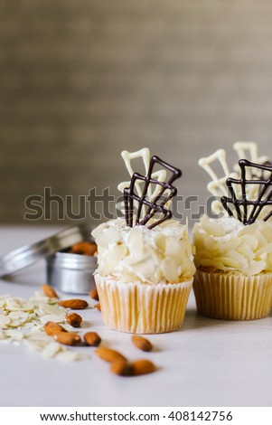 Cupcakes with white and dark chocolate on vintage table.