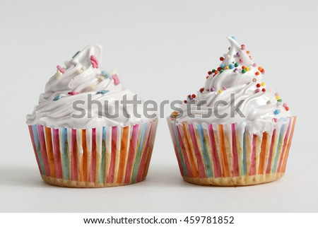 Cupcakes with white cream and sprinkles