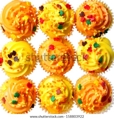 Cupcakes with yellow and orange frosting and colored sprinkles. Background. Sweet food for Halloween - stock photo
