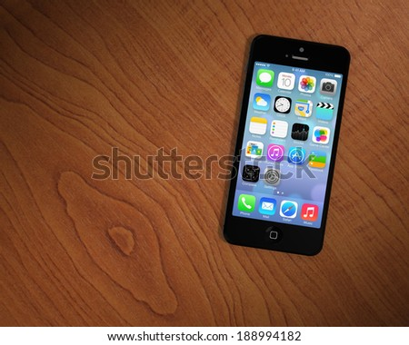 CUPERTINO, USA - APRIL 2014: An iPhone 5s on a table. Rumors on the new iPhone 6 are rising with emphasis on better specifications about the screen, touch functionality and width. - stock photo
