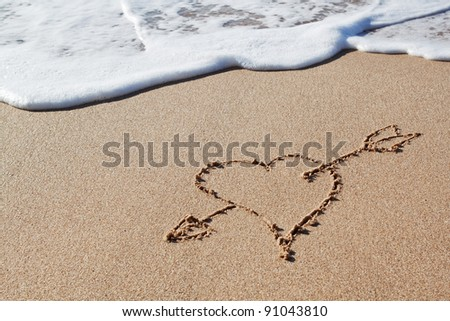 Cupid's arrow to the heart in the sand.