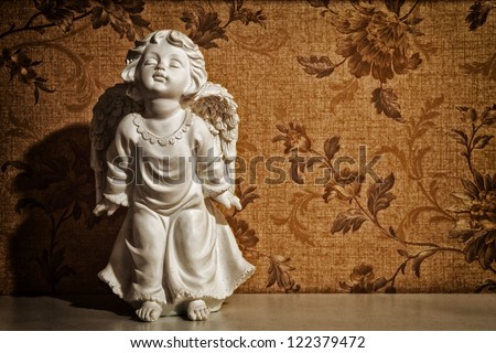 cupid sculpture with floral background vintage - stock photo