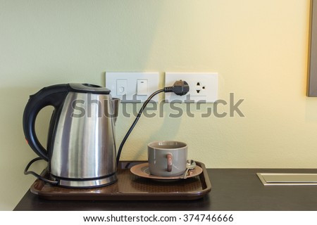 Cups and electric kettle was plugged in. - stock photo