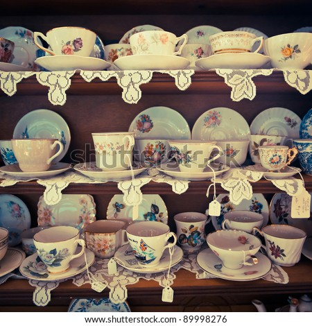 Cups and saucers on display in an antique shop. - stock photo