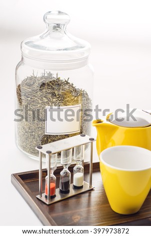 cups and teapot set with watches and loose tea in a container on white background, product for tearoom